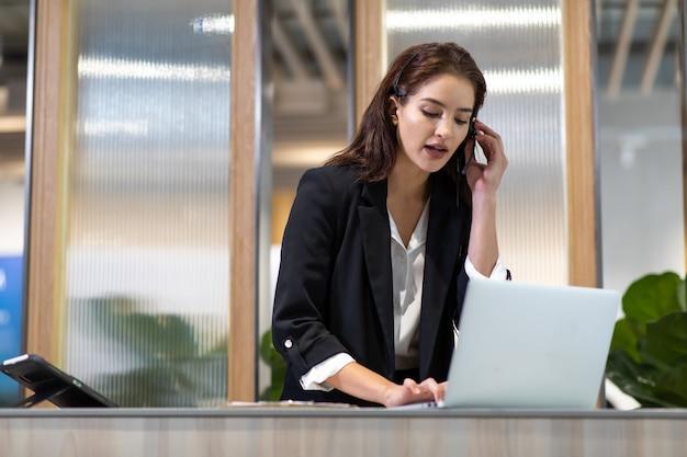 Attraktive geschäftsfrau asiatin in anzügen und headsets lächelt bei der arbeit mit computer
