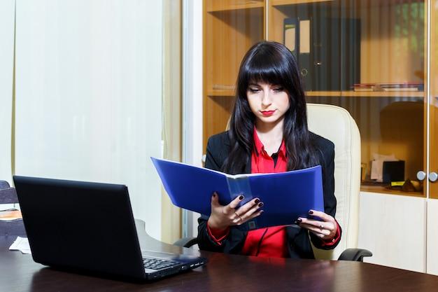Attraktive geschäftsfrau, die am arbeitsplatz im büro sitzt