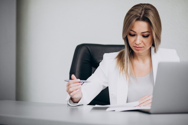 Attraktive geschäftsfrau, die am computer im büro arbeitet