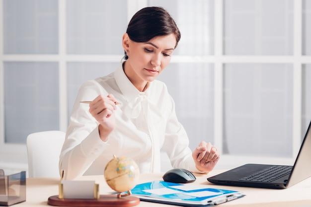 Attraktive geschäftsfrau, die am schreibtisch im büro arbeitet