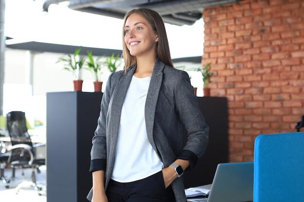 Attraktive geschäftsfrau, die bei der stellung im büro lächelt.