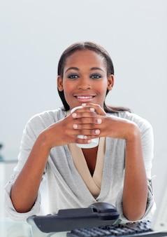 Attraktive geschäftsfrau, die einen kaffee an ihrem schreibtisch trinkt