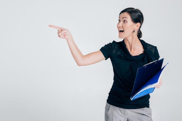 Attraktive geschäftsfrau, die einen ordner hält, der auf etwas oder copyspase auf grauem hintergrund zeigt