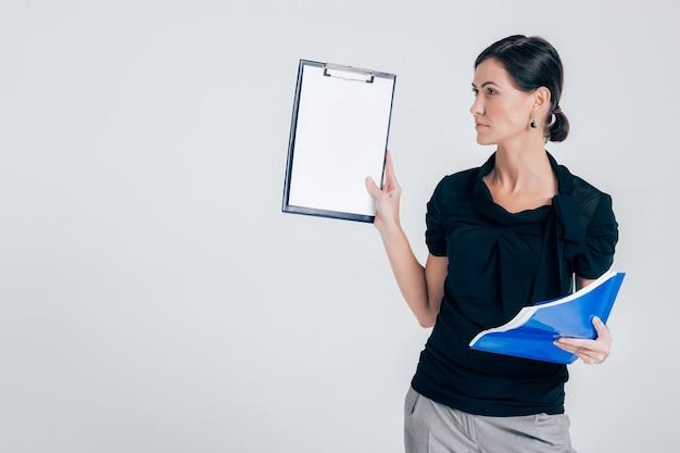 Attraktive geschäftsfrau, die einen ordner mit dokumenten auf einem grauen hintergrund hält