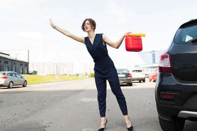 Attraktive geschäftsfrau, die einen roten kanister mit benzinkraftstoff auf einem parkplatz hält und ihre hand ausstreckt und um hilfe bittet
