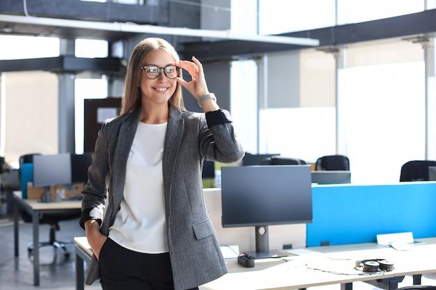 Attraktive geschäftsfrau, die ihre brille bei der stellung im büro lächelt und hält.