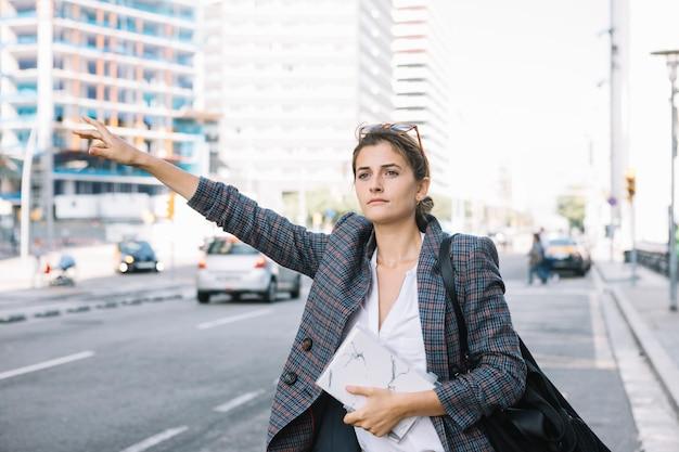 Attraktive geschäftsfrau, die ihre hand anhebt, um taxi auf stadtstraße anzurufen