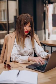 Attraktive geschäftsfrau, die in einem café am computer arbeitet