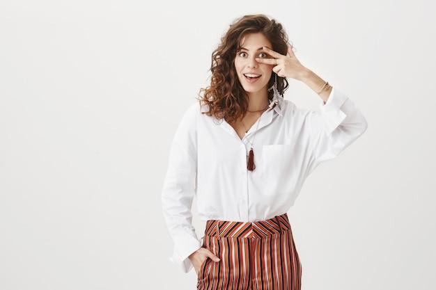 Attraktive geschäftsfrau, die lächelt und friedenszeichen zeigt