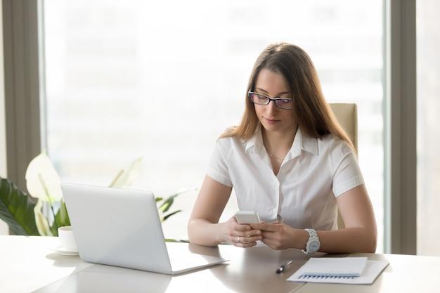 Attraktive geschäftsfrau, die smartphone, mitteilung anhält