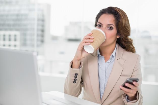 Attraktive geschäftsfrau, die von der wegwerfschale trinkt