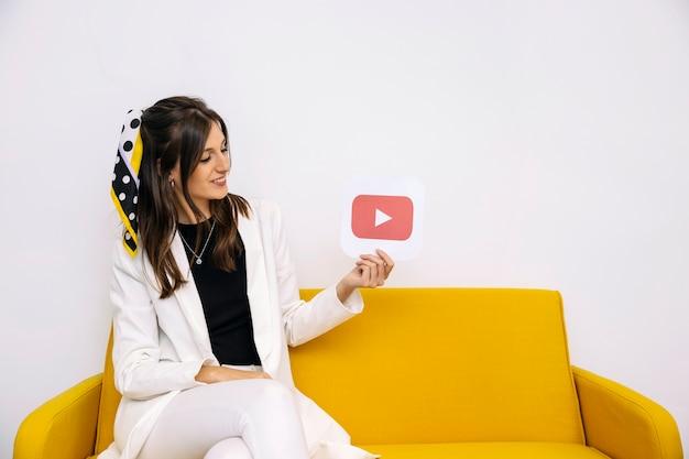 Attraktive geschäftsfrau, die youtube ikone in ihrer hand betrachtet