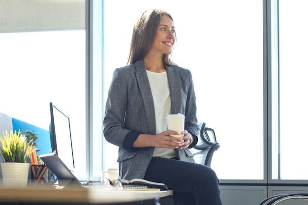Attraktive geschäftsfrau hält heißes getränk beim sitzen im büro.