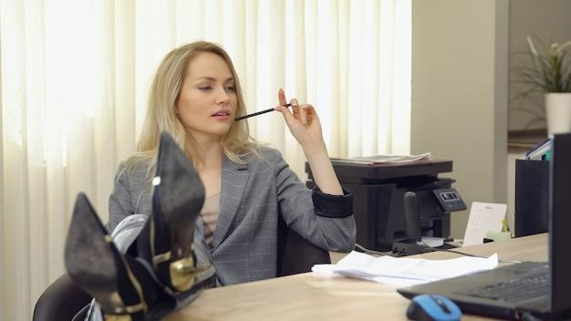 Attraktive geschäftsfrau im anzug arbeitet mit dokumenten im büro, beine auf dem tisch.
