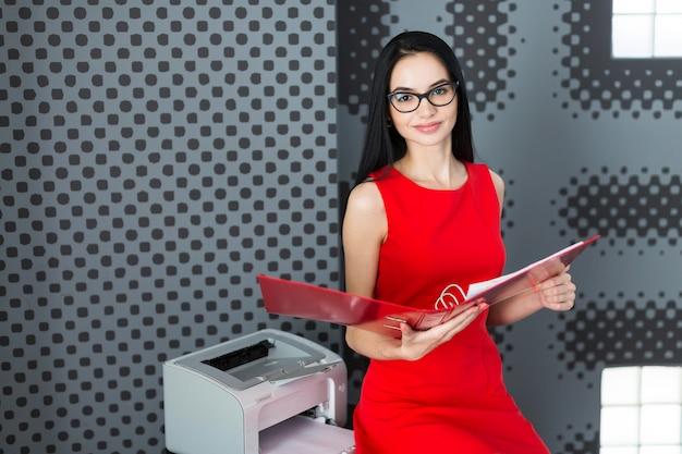 Attraktive geschäftsfrau im roten kleid und in den gläsern stehen nahe dem drucker und halten papierordner
