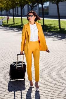 Attraktive geschäftsfrau im stilvollen gelben anzug zieht einen koffer, eilt zu einem geschäftstreffen. attraktive geschäftsfrau, die auf geschäftsreise geht und ihren koffer über den bürgersteig hinter sich zieht.