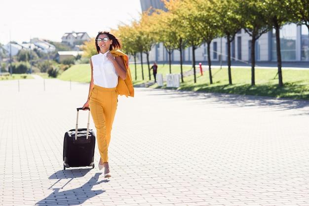 Attraktive geschäftsfrau im stilvollen gelben anzug zieht einen koffer, eilt zum flughafen. attraktive geschäftsfrau, die auf geschäftsreise geht und ihren koffer hinter sich zieht.