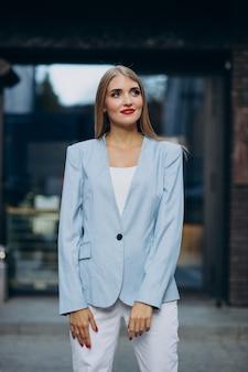 Attraktive geschäftsfrau in blauer jacke am bürozentrum