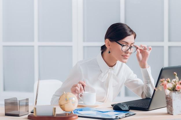 Attraktive geschäftsfrau in gläsern, die am schreibtisch im büro arbeiten