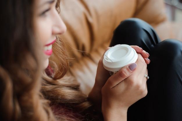 Attraktive geschäftsfrau machen eine kaffeepause auf dem sofa.
