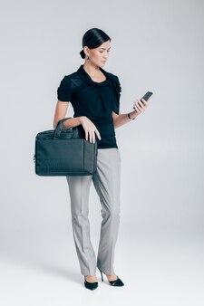 Attraktive geschäftsfrau mit einem telefon, das ordner mit dokumenten auf grauem hintergrund hält