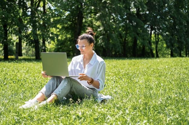 Attraktive geschäftsfrauen in den gläsern und in der weißen bluse unter verwendung des laptops, der auf gras auf bruch sitzt.