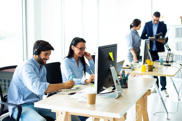Attraktive geschäftsleute in headsets lächeln, während sie in einem modernen büro mit dem computer arbeiten