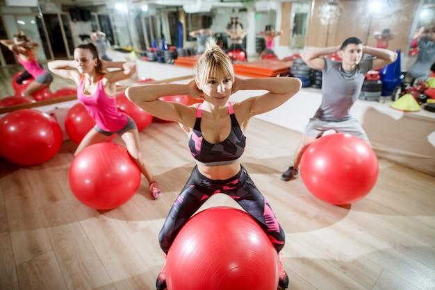 Attraktive gesunde form aktive sportliche fitnessgruppe, die übungen im fitnessstudio macht.