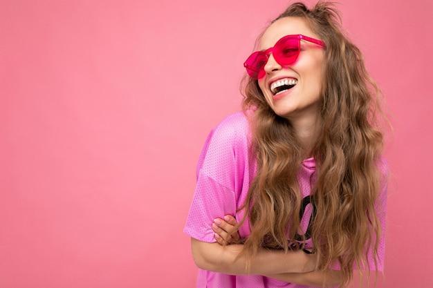 Attraktive glücklich lächelnde junge blonde frau, die alltägliche stilvolle kleidung und moderne sonnenbrillen trägt