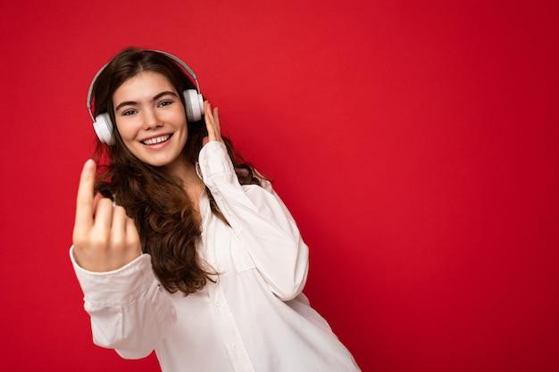 Attraktive glücklich lächelnde junge brünette weibliche person, die weißes hemd und optische brille trägt
