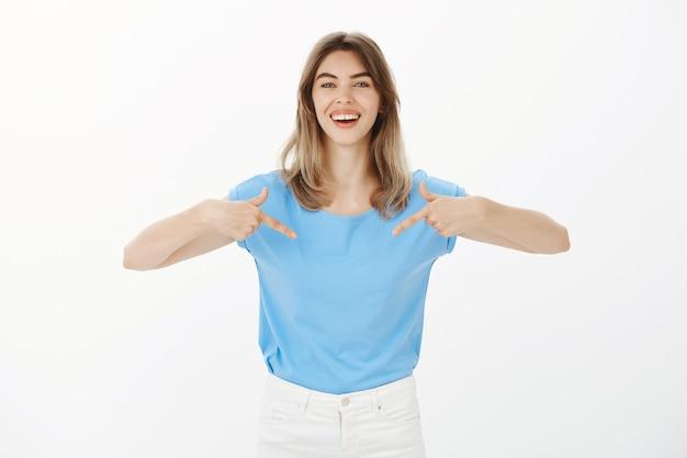 Attraktive glückliche blonde frau, die auf ihr logo zeigt und firmenbanner zeigt