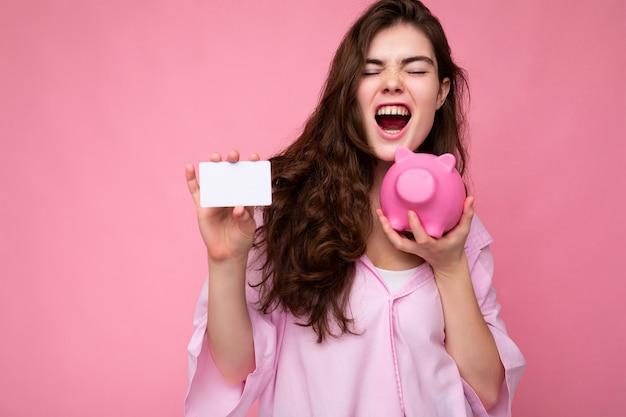 Attraktive glückliche emotionale junge brunettefrau, die hemd einzeln auf rosafarbenem hintergrund mit leerem trägt