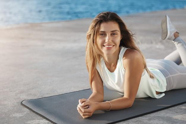 Attraktive glückliche entspannte athletensportfrau, die übungsyogamatte nahe dem meer liegt, das kai-training genießt