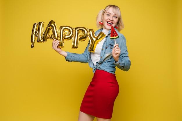 Attraktive glückliche frau, die große goldbuchstaben lacht, die am gelben studiohintergrund aufwerfen