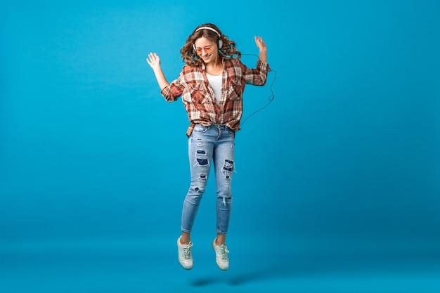 Attraktive glückliche frau, die in der fröhlichen stimmung springt, die musik in den kopfhörern im karierten hemd und in den jeans lokalisiert auf blauem studiohintergrund hört