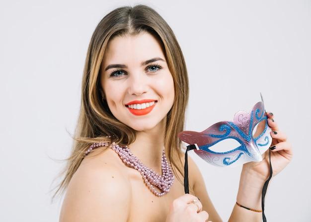 Attraktive glückliche frau, die karnevalsmaske auf weißem hintergrund hält