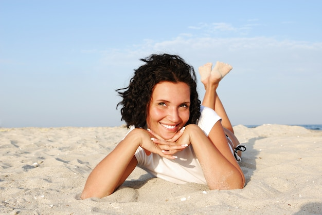 Attraktive glückliche frau, die unten am strand liegt und kamera betrachtet