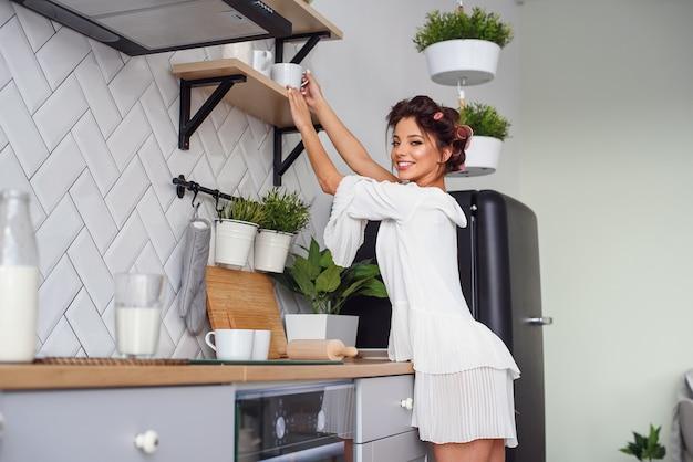 Attraktive glückliche frau im weißen bademantel in der gemütlichen küche am morgen gekleidet. verführerisches junges mädchen hat morgenkaffee.