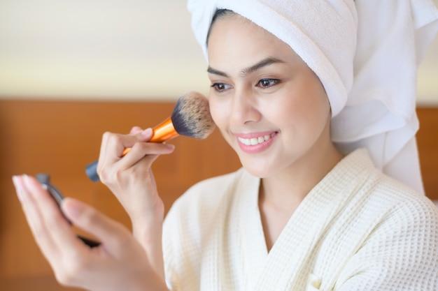 Attraktive glückliche frau im weißen bademantel trägt natürliches make-up mit kosmetischem puderpinsel beauty concept auf.
