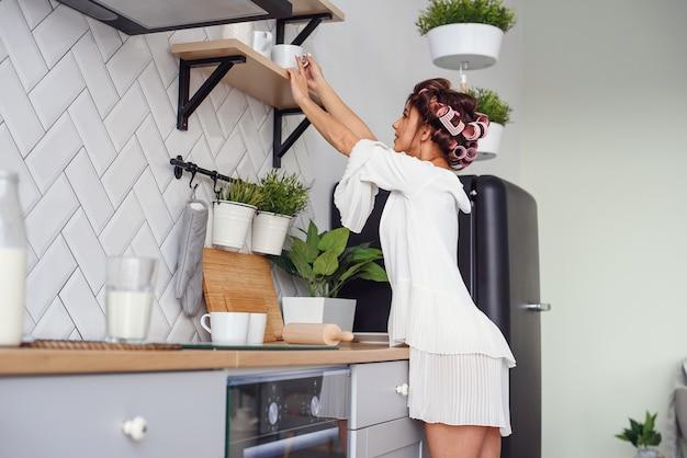Attraktive glückliche frau nimmt am morgen eine tasse aus einem regal in der küche.