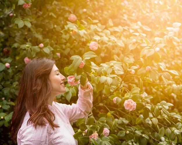 Attraktive glückliche frau, welche die rosa blume wächst auf grünem zweig hält