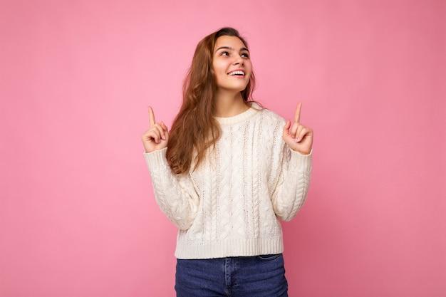 Attraktive glückliche freudige lächelnde junge dunkelblonde lockige frau in lässiger weißer strickjacke sexy sorglos
