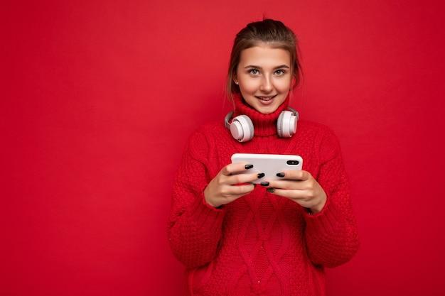 Attraktive glückliche junge brünette frau, die roten pullover lokalisiert über rotem hintergrundwand hält und handy-surfen im internet und tragen von bluetooth-kopfhörern mit blick auf die kamera trägt.
