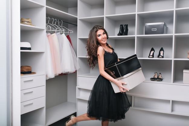 Attraktive glückliche junge frau kaufte gerade neue schuhe, hielt kisten in den händen, stand im ankleidezimmer, kleiderschrank. sie lächelt und schaut. sie trägt ein schwarzes kleid mit einem flauschigen rock.