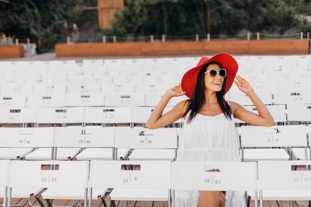 Attraktive glückliche lächelnde frau gekleidet in weißem kleid, rotem hut, sonnenbrille, die im sommer freilufttheater auf stuhl allein, frühlingsstraßenart-modetrend sitzt