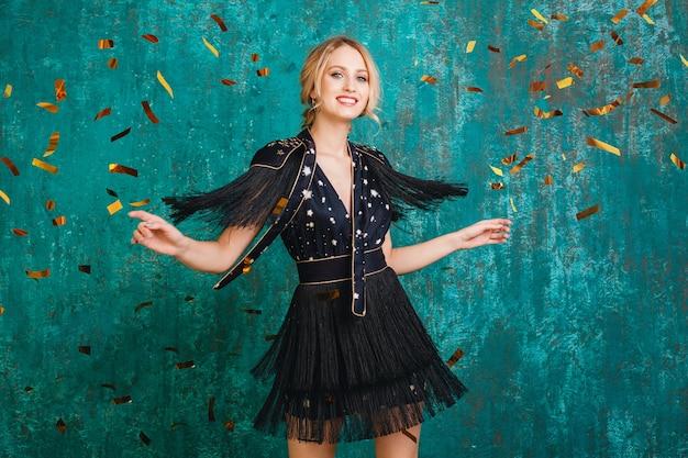 Attraktive glückliche lächelnde frau im stilvollen schwarzen kleid