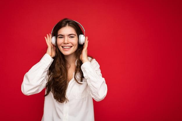 Attraktive glückliche lächelnde junge brünette weibliche person, die weißes hemd und optische brille trägt