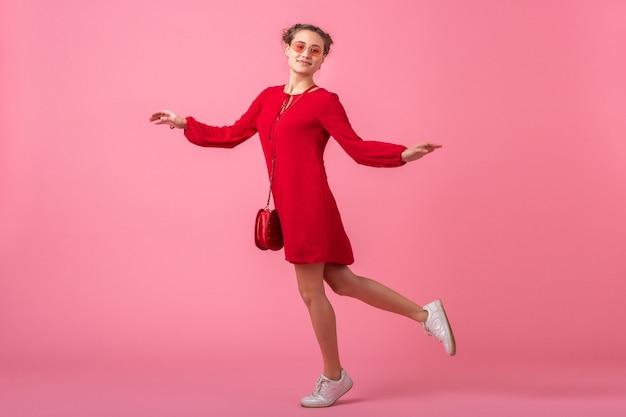 Attraktive glückliche lächelnde stilvolle frau im roten trendigen kleid, das auf rosa wand läuft, isoliert, frühlingssommer-modetrend, romantische stimmung flirty mädchen springt
