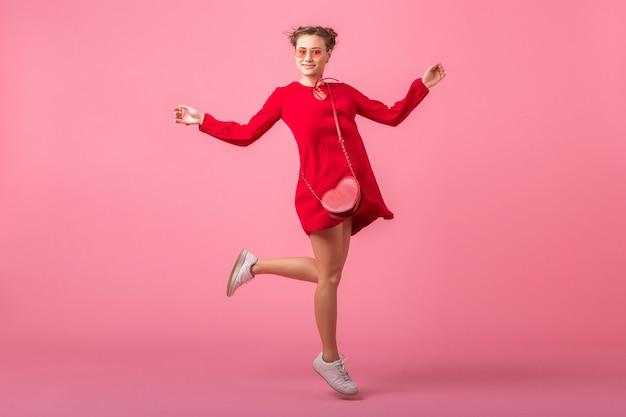 Attraktive glückliche lächelnde stilvolle frau im roten trendigen kleid, das auf rosa wand läuft, lokalisiert, frühlingssommer-modetrend, tag der heiligen valenite, romantisches stimmungsflirtmädchen