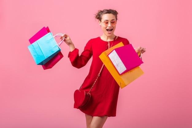 Attraktive glückliche lächelnde stilvolle frau shopaholic im roten trendigen kleid, das bunte einkaufstaschen auf rosa wand lokalisiert, verkauf aufgeregt, modetrend hält